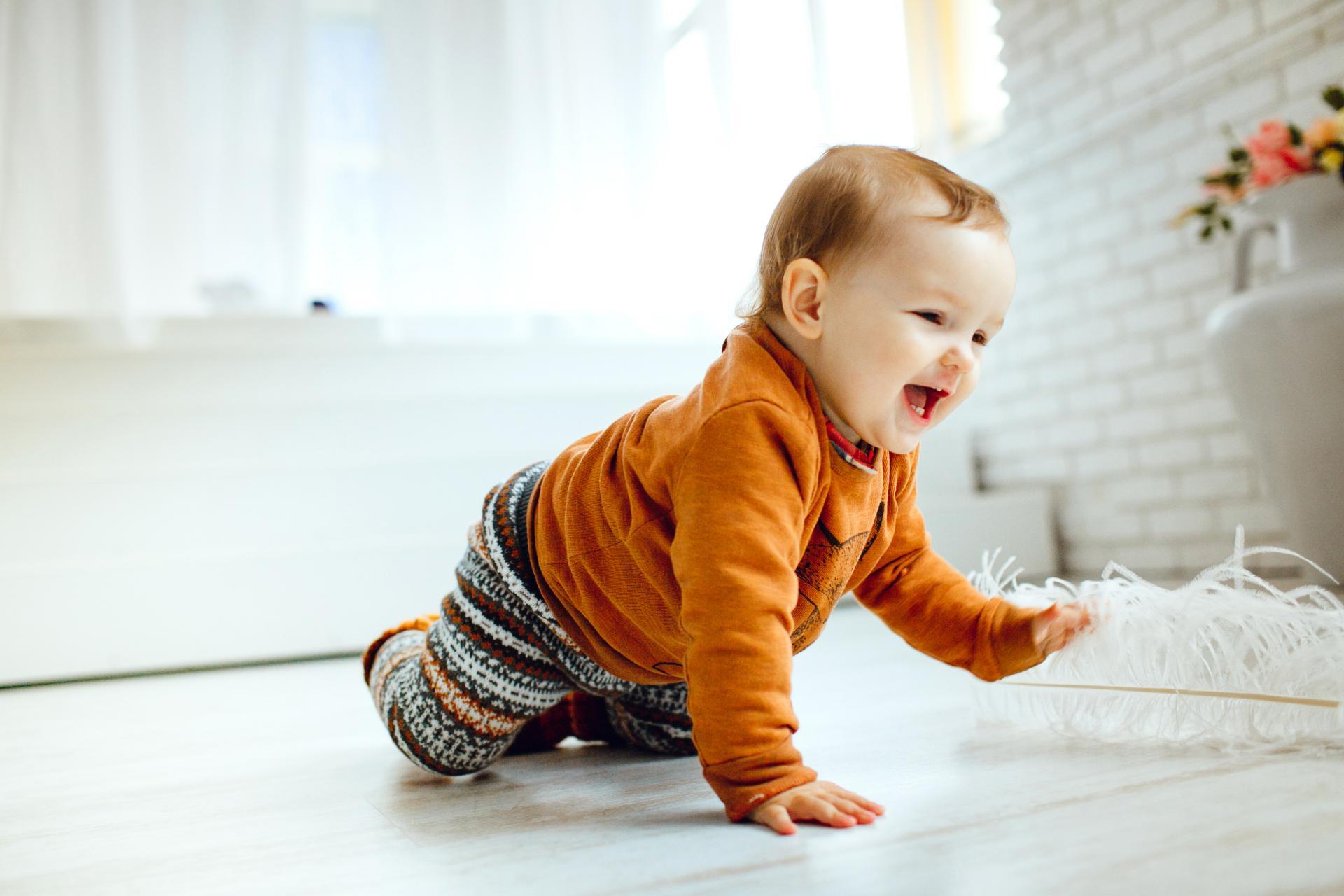 Happy child orange sweater plays with feather floor